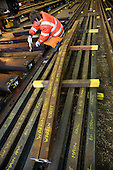 A worker in the Points and Crossings Shed of London Underground's  Lillie Road Depot begins assembly of a new crossing.  The depot produces replacement track for the tube network and offers a same day service for 'urgencies and emergencies'.  The depot is now run by London Underground following the collapse of PPP contractor Metronet in 2007.