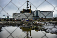 """4th block of Chernobyl power plant protected by concrete wall seen through bars deviding """"relatively safe"""" territory of the construction and """"restricted industrial"""" zone with higher doses of radioactive emission. Workers of the CNPP in private conversation admit that such division is created by the company only for not paying addition to salary for work in dangerous conditions."""