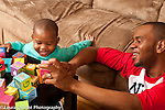 Two year old toddler boy at home with father playing with alphabet blocks