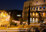 Rush hour traffic zips past the ancient Roman Colosseum at sunset in Rome, Italy.