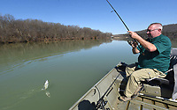 Mike McBride reels in one of several crappie he caught March 4 2021 at Lake Sequoyah in Fayetteville. Small silver and black jigs rigged three feet under a float did the trick. McBride says fishing will get even better as spawning time nears.<br />(NWA Democrat-Gazette/Flip Putthoff)