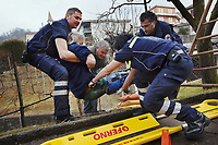 Switzerland. Canton Ticino. Comano. Paramedics team carry an injured man on an emergency medical stretcher. The man was cutting branches off a tree, fell on the ground and broke his right leg. He is brought to hospital for medical surgery and recovery. Three paramedics wear blue uniforms and work for theCroce Verde Lugano. Both men are professional certified nurses, the woman (R) is a volunteer specifically trained in emergency rescue. TheCroce Verde Lugano is a private organization which ensure health safety by addressing different emergencies services and rescue services. Volunteering is generally considered an altruistic activity where an individual provides services for no financial or social gain to benefit another person, group or organization. Volunteering is also renowned for skill development and is often intended to promote goodness or to improve human quality of life. 27.01.2018 © 2018 Didier Ruef
