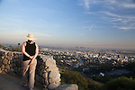 A woman at a Viewpoint on Mulholland Drive with a view of Hollywood and Downtown Los Angeles, CA