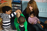 Education Preschool 3 year olds female teacher playing with two boys building with wooden blocks, girl observiing from her lap