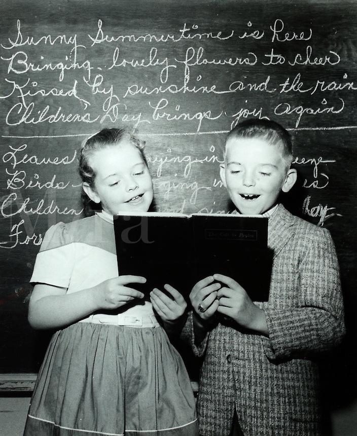 Girl and boy singing by blackboard in classroom. 1950's.