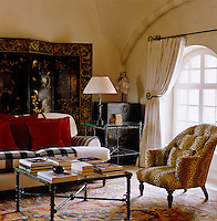 An armchair upholstered in leopard print fabric and lacquered Chinese screen and box behind a contemporary sofa furnish this cosy sitting room