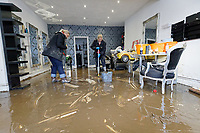 Pictured L-R: Laura Court and Louise Bedgood clear up mud from the floor of Lougos hair dressers. Monday 17 February 2020<br /> Re: Cleanup after storm Dennis in Oxford Street, Nantgarw, Wales, UK.