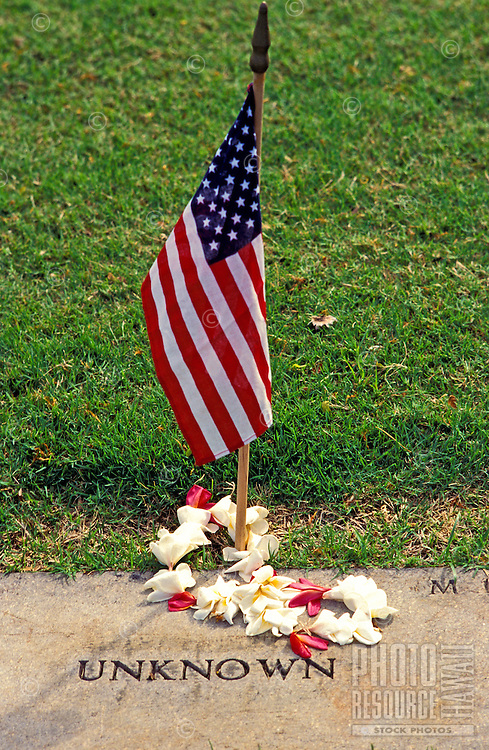 A plumeria lei encircles an American flag marking the grave of an unknown soldier at Punchbowl National Cemetery in Honolulu, Hawaii.