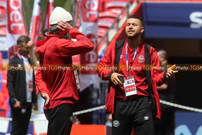 Emiliano Marcondes of Brentford enjoys the music coming from the headphones of Mathias Jensen ahead of kick-off during Brentford vs Swansea City, Sky Bet EFL Championship Play-Off Final Football at Wembley Stadium on 29th May 2021