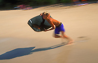 Blurred motion image of a boy as he runs on the beach holding his boogie board. Hawaii.