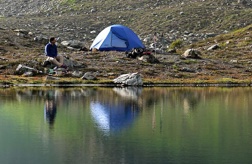 Man sitting beside tent and alpine lake, near Yellow Aster Butte, North Cascades, Whatcom County, Washington, USA.