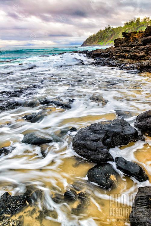 Kahili Beach shoreline and lava rocks accentuated by incoming surf and distant headlands, Kaua'i.