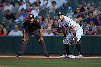 Charlotte Knights first baseman Matt Skole (12) on defense as umpire Erich Bacchus looks on during the game against the Indianapolis Indians at BB&T BallPark on May 26, 2018 in Charlotte, North Carolina. The Indians defeated the Knights 6-2.  (Brian Westerholt/Four Seam Images)