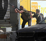Shiite fighters from Hezbollah and Amal movements takes aim with a Kalashnikov assault rifle amidst clashes in the area of Tayouneh, in the southern suburb of the capital Beirut, on October 14, 2021. - Gunfire killed several people and wounded 20 at a Beirut rally organised by the Shiite Hezbollah and Amal movements to demand the dismissal of the Beirut blast lead investigator, the state-run National News Agency said. Photo by Haitham Moussawi