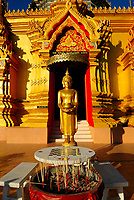 Incense sticks in front of a Buddha statue in front of a temple near Chiang Mai, Thailand, Southeast Asia.