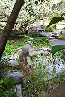 Stone statue overlooking pond in shade of trees in Norfolk Botanical Garden