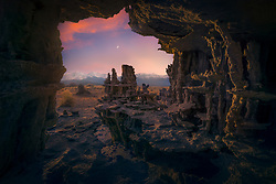 A view through a small tufa cave at the unique formations and mountain range in the distance.