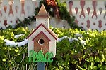 Birdhouse with 'peace' holiday decoration.