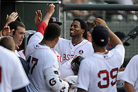 Outfielder Aneury Tavarez (5) of the Greenville Drive is congratulated in the dugout after scoring a run in a game against the Charleston RiverDogs on Wednesday, June 12, 2013, at Fluor Field at the West End in Greenville, South Carolina. Charleston won, 10-5. The teams wore their Boston and New York affiliate uniforms as part of a promotion. (Tom Priddy/Four Seam Images)