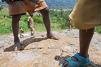 """Kamengeri's Rock. """"My grandfather told me this story. At the time I was ten and he was old like I am now. King Rwogero had a goatherd named Kamangeri  and this goatherd was trading away the kings goats for cows.  The king summoned   Kamangeri to  the palace and asked ' What would you do if if someone betrayed you?' Kamangere  answered, ' I would heat a rock until it pulsed red. Then burn the man on the rock.'  The king had villagers stoke fire on these rocks for 30 days. Then he summoned Kamengeri to his fate."""" - An old man. Photo by Brendan Bannon. Rwanda Feb 28, 2014"""