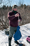 New Hampshire Fish and Game Biological Technician, Brett Ferry weighs a trapped New England cottontail rabbit inside the Great Bay National Wildlife Refuge.