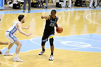 CHAPEL HILL, NC - FEBRUARY 24: Koby McEwen #25 of Marquette is defended by Andrew Platek #3 of North Carolina during a game between Marquette and North Carolina at Dean E. Smith Center on February 24, 2021 in Chapel Hill, North Carolina.