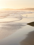 Distant silhouettes of two people, woman and child, on the beach at low tide of the ocean, Green Point, Pacific Rim National Park Reserve, Long Beach, Tofino, Vancouver Island, BC, Canada Image © MaximImages, License at https://www.maximimages.com