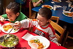 Education preschool 3-4 year olds two boys serving eating lunch at HeadStart program spagetti with tomato sauce and peas, serving self