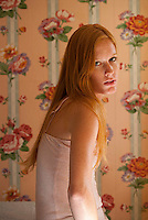 Young redheaded woman seated in room with floral wallpaper