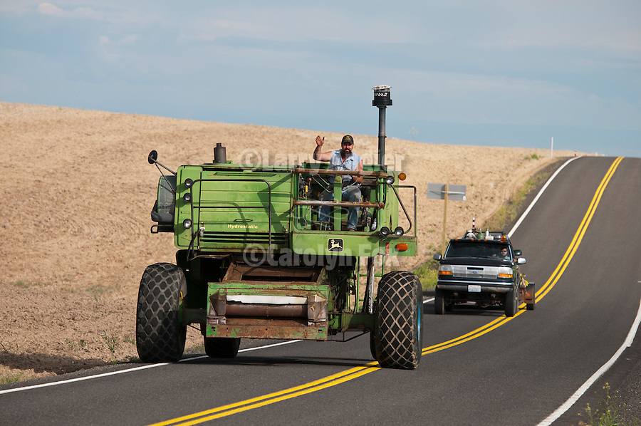 """Jeff Yerbich and his team heard """"Free Beer (Tomorrow)"""" their vintage John Deere combine on the road from their farm in Kahlotus, Wash. to the combine destruction derby in Lind, Wash. about 25 miles away through the rolling wheat fields along Washington SR 21"""