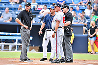 First base umpire Emil Jimenez, Asheville Tourists manager Warren Schaeffer (13), Rome Braves manager Randy Ingle (12) and home plate umpire Mike Snover go over the ground rules before a game between the Rome Braves and the Asheville Tourists at McCormick Field on July 27, 2017 in Asheville, North Carolina. The Braves defeated the Tourists 6-3. (Tony Farlow/Four Seam Images)