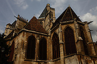 Paris Right Bank: The top of the back of the Saint Gervais church (XVI-XVII century) in the Marais, with its high glass windows, its typical ancient roof and its gargoyles. There was a typical Parisian sky with sun and clouds, too.