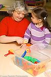 Education preschool 2-3 year olds vertical female volunteer aide with children