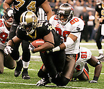 December 2009: Tampa Bay Buccaneers cornerback Ronde Barber (20) tackles New Orleans Saints running back Mike Bell (21) during an NFL football game at the Louisiana Superdome in New Orleans.  The Buccaneers defeated the Saints 20-17.