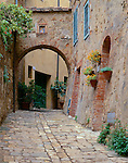 Tuscany, Italy<br /> Street scene with stone walls, walkway and arched passage in the hill town of San Quirico d'Orcia