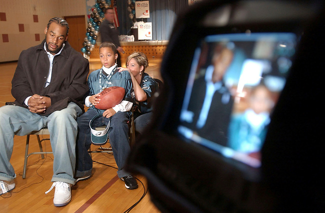 """Donavon McNabb, left, waits with Andrew Butler, center, to do a live ESPN TV interview at the Oak Ridge Elementary School Tuesday, Oct. 19, 2004 in Harleysville, Pa. Butler fifth grader t the school won a sweepstakes """"Take A Player to School',  McNabb was his chice of player to vist his class. The woamn at right is the scholols Physical education teacher Colleen Wegimont who helped Butler manage his stage fright. (The Philadelphia Daily News/Bradley C Bower)"""