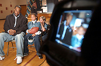 "Donavon McNabb, left, waits with Andrew Butler, center, to do a live ESPN TV interview at the Oak Ridge Elementary School Tuesday, Oct. 19, 2004 in Harleysville, Pa. Butler fifth grader t the school won a sweepstakes ""Take A Player to School',  McNabb was his chice of player to vist his class. The woamn at right is the scholols Physical education teacher Colleen Wegimont who helped Butler manage his stage fright. (The Philadelphia Daily News/Bradley C Bower)"