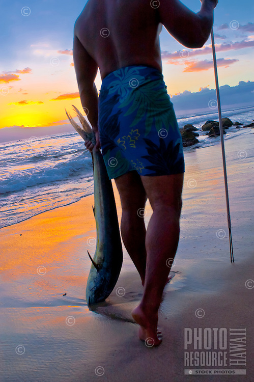 Local fisherman with his catch returning from the sea at sunset, Ka'anapali, Maui