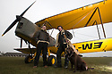 """13/03/15<br /> <br /> L/R: Tim Cox (Deputy Chief Flight Instructor) and Will Flanagan (Chief Flight Instructor), with Blue Eye Aviations' mascot, Labrador, Tess.<br /> <br /> ***FULL STORY HERE:   http://www.fstoppress.com/articles/tiger-moth-restorations/    ****<br /> <br /> You may remember spending hours toiling over Airfix models, painstakingly following intricate instructions and trying not to glue your fingers together before painting your own miniature version of one of the RAF's or Luftwaffe's finest aircraft. Then spare a thought for one man who has just helped to restore and put together one World War Two Tiger Moth and is about to start piecing together another FOUR aircraft that were discovered in bits in a barn.<br /> <br /> Sixty-year-old Colin Temple-Smith – who wears a moustache that any Wing Commander would be proud of – has spent a lifetime restoring vintage cars and motorcycles and recently quit his job as a window fitter to help re-build the five bi-planes that will become part of a growing fleet of Tiger Moths at Derbyshire based Blue Eye Aviation.<br /> <br /> Today saw the first of the fully-restored five aircraft take to the skies.<br /> <br /> """"It's just like working on old bikes and cars, although they're a lot more fragile"""" explained Colin, whose wife runs the Aviators Café at Darley Moor Airfield near Ashbourne.<br /> <br /> """"When I was a teenager I used to be a member of a modelling club, making flying models from wood and canvas. They're very similar to build – it's really just the size that's changed with these.<br /> <br /> All Rights Reserved: F Stop Press Ltd. +44(0)1335 418629   www.fstoppress.com."""