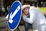 © Joel Goodman - 07973 332324 . 29/08/2015 . Manchester , UK . The actor , SIR IAN MCKELLEN , ducks behind a street sign to light a cigarette as he leads the 2015 Manchester Pride parade . Photo credit : Joel Goodman