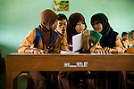 School girls at an Islamic boarding school in Lombok, Indonesia look at their report cards.