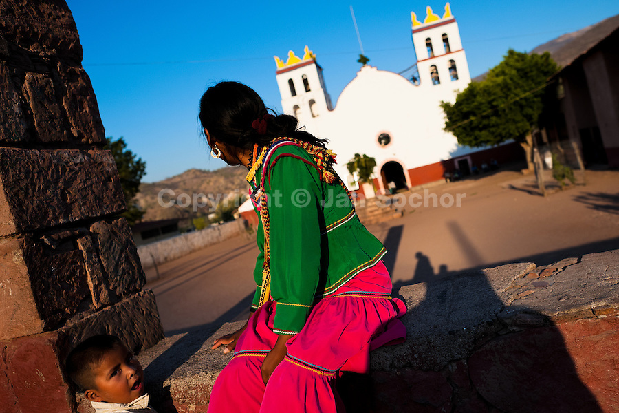 """A Cora Indian woman sits in front of the church before the religious ritual ceremony of Semana Santa (Holy Week) in Jesús María, Nayarit, Mexico, 20 April 2011. The annual week-long Easter festivity (called """"La Judea""""), performed in the rugged mountain country of Sierra del Nayar, merges indigenous tradition (agricultural cycle and the regeneration of life worshipping) and animistic beliefs with the Christian dogma. Each year in the spring, the Cora villages are taken over by hundreds of wildly running men. Painted all over their semi-naked bodies, fighting ritual battles with wooden swords and dancing crazily, they perform demons (the evil) that metaphorically chase Jesus Christ, kill him, but finally fail due to his resurrection. La Judea, the Holy Week sacred spectacle, represents the most truthful expression of the Coras' culture, religiosity and identity."""