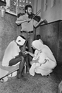 """Calcutta, India. April 04, 1975.<br /> Mother Teresa comforts injured man while a violinist plays behind them at her Kalighat Home for the Dying in Calcutta. The first Home for the Dying opened in 1952 and was a free hospice for the poor. Mother Teresa (Agnes Gonxha Boyaxihu) the Roman Catholic, Albanian nun revered as India's """"Saint of the Slums,"""" was awarded the 1979 Nobel Peace Prize."""