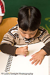 Education preschoool children ages 3-5 art activity boy drawing with crayon held in fist grip vertical