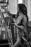 Black and white portrait fo a beautiful young woman sumi-e artist with an easel painting half nude in comfort of her home studio wearing just a light see-thorugh robe over her naked body Image © MaximImages, License at https://www.maximimages.com