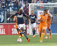 Houston Dynamo midfielder Tony Cascio (28) clears the ball as New England Revolution midfielder Saer Sene (39) closes. In a Major League Soccer (MLS) match, the New England Revolution (blue/white) defeated Houston Dynamo (orange), 2-0, at Gillette Stadium on April 12, 2014.