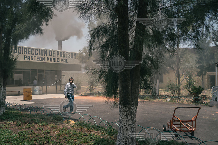 A man walks away from a public cemetery building while smoke from its crematorium billows out from the chimney.