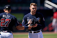 Atlanta Braves first baseman Freddie Freeman (5) gets his hat and glove from third baseman Austin Riley (27) in between innings during a Major League Spring Training game against the Boston Red Sox on March 7, 2021 at CoolToday Park in North Port, Florida.  (Mike Janes/Four Seam Images)