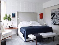 The master bedroom has a light and airy feel with white panelled walls and cool blue and grey accents. A 1960s bench by Harvey Probber, upholstered in a Holly Hunt fabric, stands at the end of the double bed. Silver angle-poise lamps stand on the bedside tables.