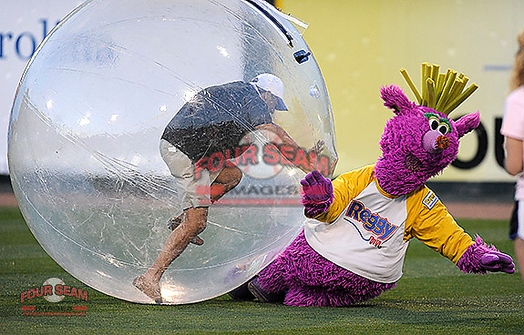A fan knocks over Reggy the Purple Party Dude during a between-innings stunt during a game between the Greenville Drive and the Charleston River Dogs on Saturday, April 6, 2013, at Fluor Field at the West End in Greenville, South Carolina. Greenville won Game 2 of a doubleheader, 8-4. (Tom Priddy/Four Seam Images)